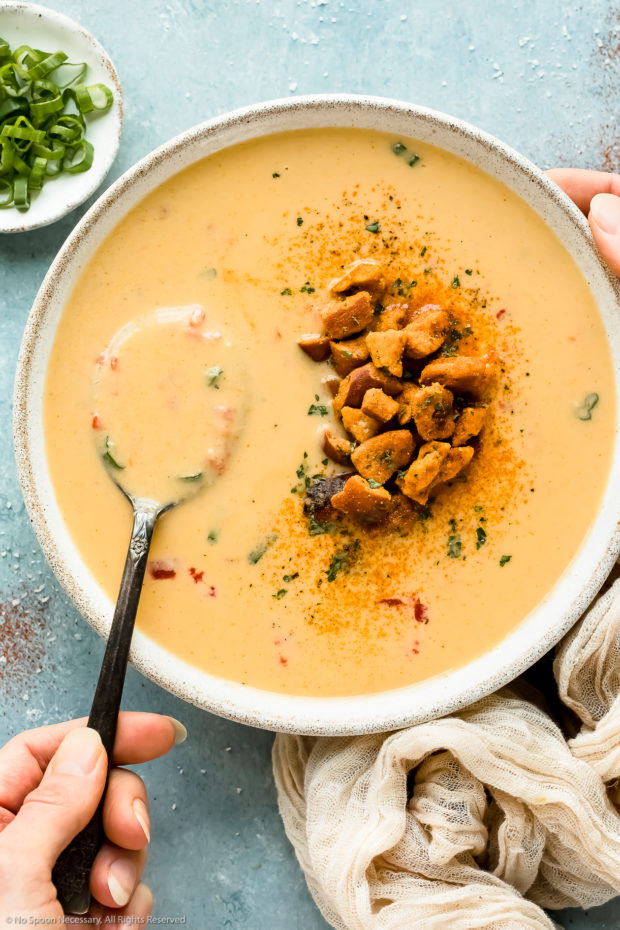 Overhead photo of beer cheddar soup topped with pretzel pieces in a white bowl with a hand holding a spoon inserted into the soup.