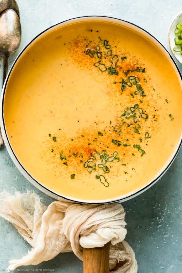 Overhead photo of beer cheese soup garnished with smoked paprika and sliced scallions in a white saucepan with soup spoons and a ramekin of sliced scallions next to the pan.
