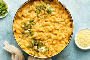 Overhead photo of Healthy Mac and Cheese garnished with sliced scallions in a white saucepan with ramekins of sliced scallions and grated cheese next to the pan.