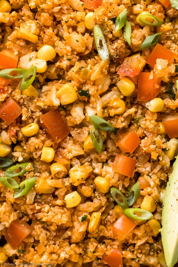 Overhead, extreme close-up photo of Mexican-style rice made with cauliflower, corn and tomatoes.