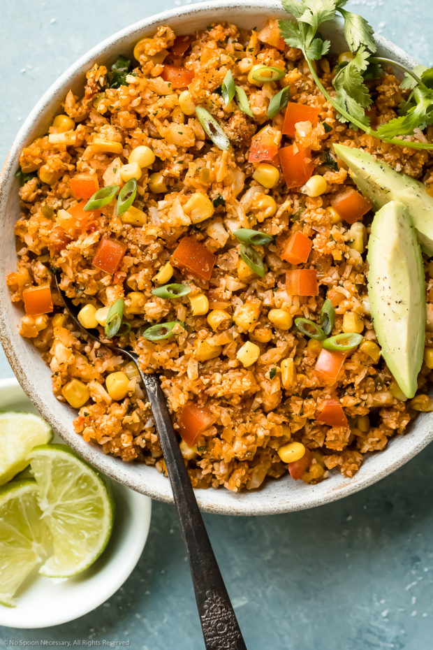 Overhead, close-up photo of low-carb Arroz Rojo garnished with fresh cilantro and avocado slices and a serving spoon inserted into the rice.