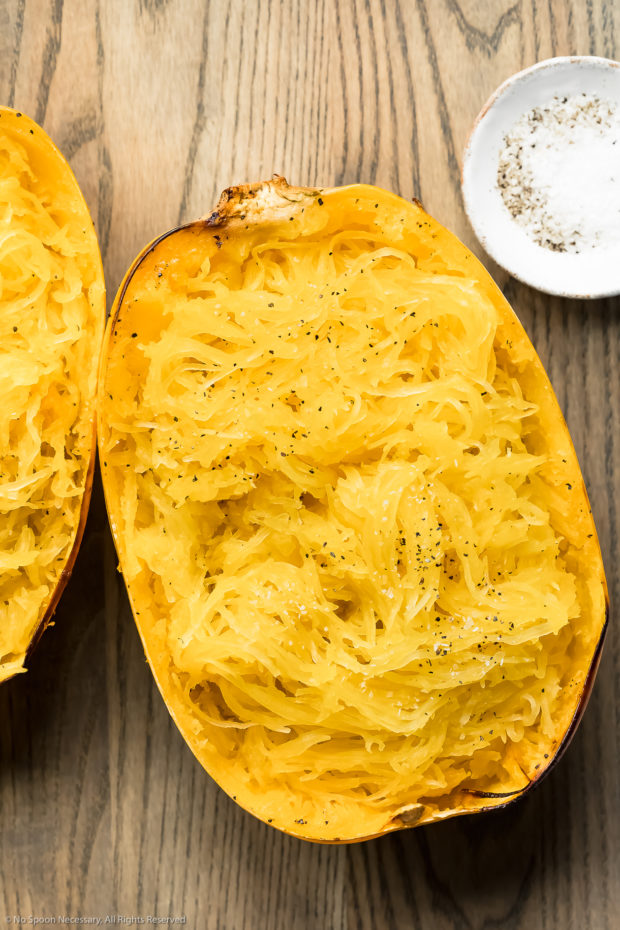 Overhead photo of a half of a roasted spaghetti squash that has been scraped with a fork to showcase the spaghetti-like strands.
