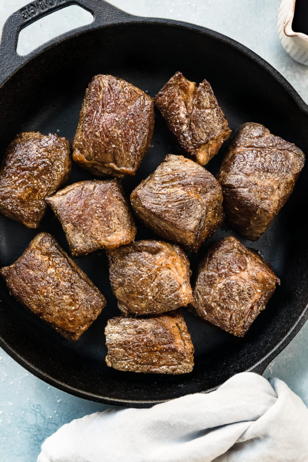 Overhead photo of seared, browned boneless beef short rib pieces in a cast iron pan with a ramekin of red wine next to the pan - photo of step 2 of the recipe.