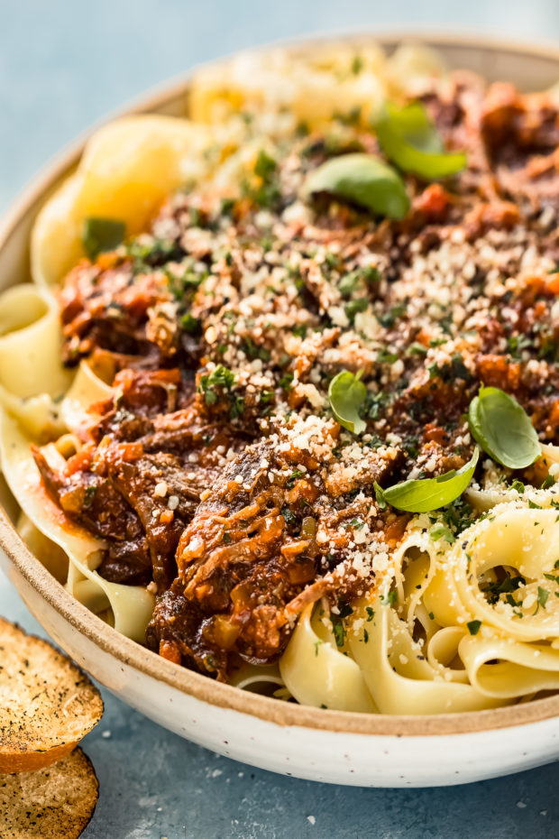 Angled, close-up photo of Slow Cooker Ragu Bolognese over papparelle pasta in a neutral colored serving bowl with slices of toasted baguette in front of the bowl and a ramekin of grated parmesan cheese blurred behind the bowl.