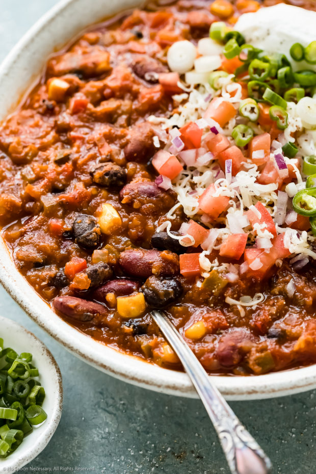 Angled close-up photo of Vegetarian 3 Bean Chili garnished with shredded white cheddar cheese, diced tomatoes and scallions in a white bowl with a spoon inserted into the chili and a ramekin of sliced scallions next to the bowl.