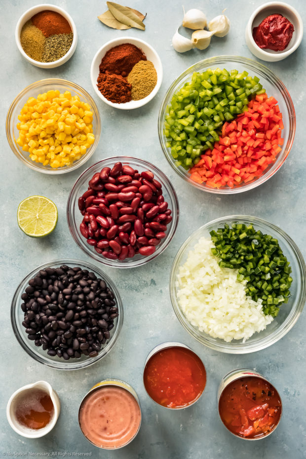Overhead photo of all the ingredients needed to make three bean chili neatly arranged in individual glass bowls on a blue surface.