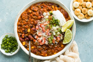 Overhead landscape photo of Vegetarian Bean Chili garnished with shredded cheese, diced tomatoes, scallions, lime wedges and a dollop of sour cream in a white bowl; with a pale neutral colored napkin and ramekins of oyster crackers and sliced scallions next to the bowl.