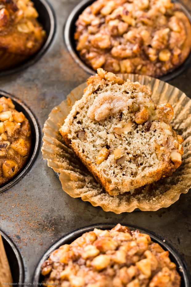Angled, close-up photo of a Banana Nut Muffin cut in half and smeared with a dollop of cinnamon honey butter.