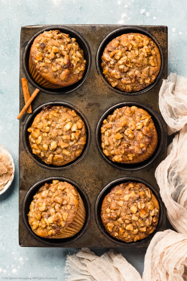 Overhead photo of Banana Nut Muffins in a metal 6 count muffin pan with a ramekin of honey cinnamon butter and a light tan linen next to the pan.