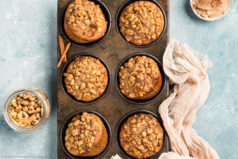 Overhead photo of Banana Nut Muffins in a metal 6 count muffin pan with a ramekin of honey cinnamon butter, jar of walnuts and a light tan linen next to the pan.