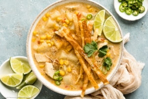 Overhead landscape photo of Chicken Corn Chowder topped with crispy tortilla strips and lime wedges in a white bowl with ramekins of sliced jalapenos and lime wedges next to the bowl.