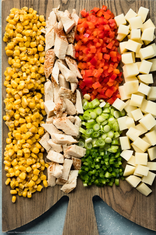 Overhead photo of the main ingredients in chicken chowder - corn, diced cooked chicken, diced peppers, sliced scallions and diced potatoes - neatly arranged on a gray wood board.