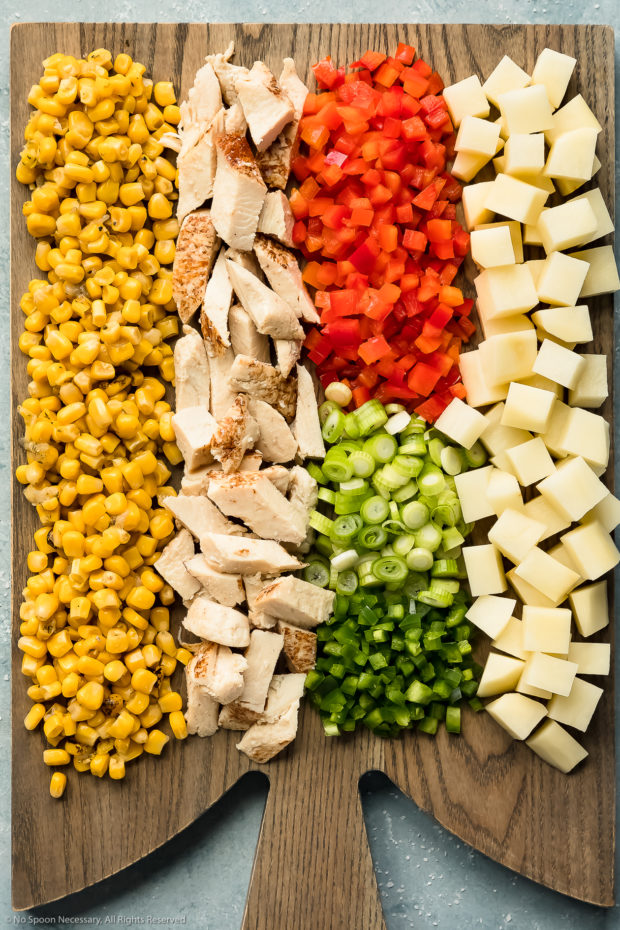 Overhead photo of corn, diced cooked chicken, diced peppers, sliced scallions and diced potatoes neatly arranged on a gray wood board - photo of all the main ingredients in chicken chowder.