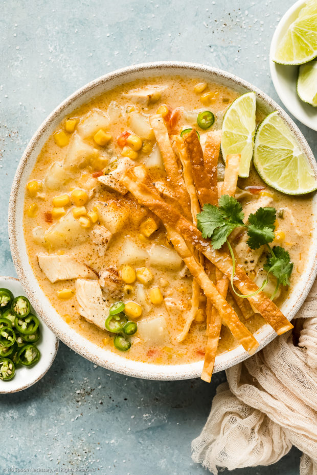 Overhead photo of Chicken Corn Chowder topped with crispy tortilla strips and lime wedges in a white bowl with ramekins of sliced jalapenos and lime wedges next to the bowl.