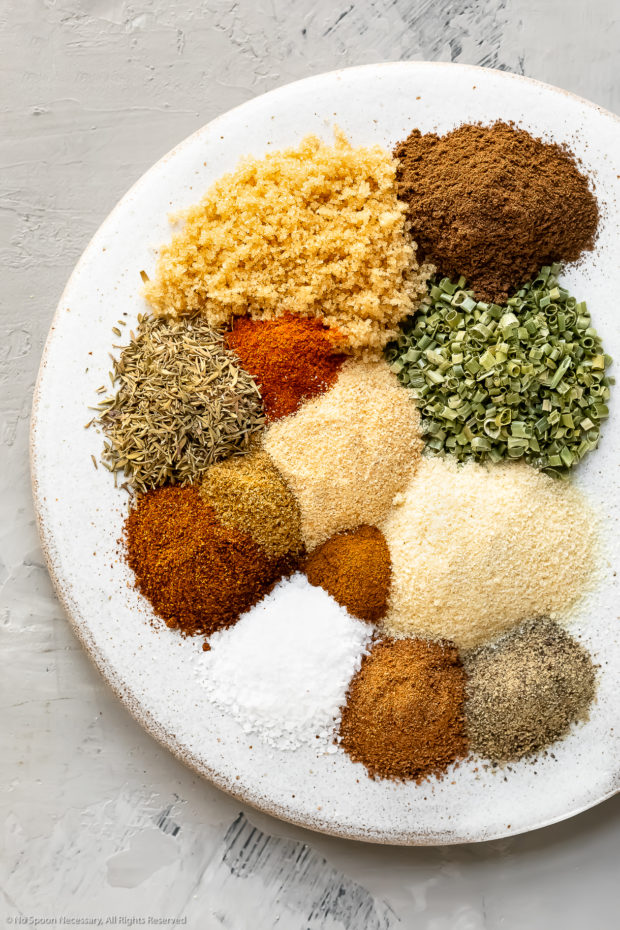 Overhead photo of all the spices in Jerk Seasoning neatly organized on a white plate with the name of each individual spice written out.