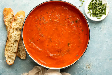 Overhead photo of creamy vodka sauce in a white saucepan with slices of crusty baguette and a ramekin of thinly sliced fresh basil next to the pan.