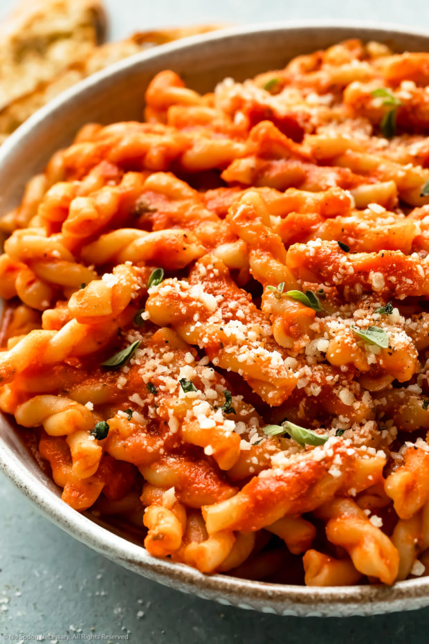 Angled, up-close photo of cooked gemelli pasta tossed with vodka sauce in a white bowl - photo of one way to use vodka sauce.