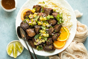 Overhead photo of a plate of Jamaican Jerk Pork topped with tropical salsa on a bed of white rice with orange slices; with a neutral colored linen, cup of jerk sauce and ramekin of lime wedges next to the plate.