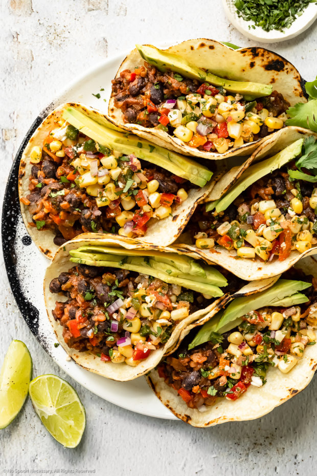 Overhead photo of black bean tacos topped with corn salsa and slices of avocado on a white plate with a ramekin of chopped cilantro and fresh lime wedges next to the plate.