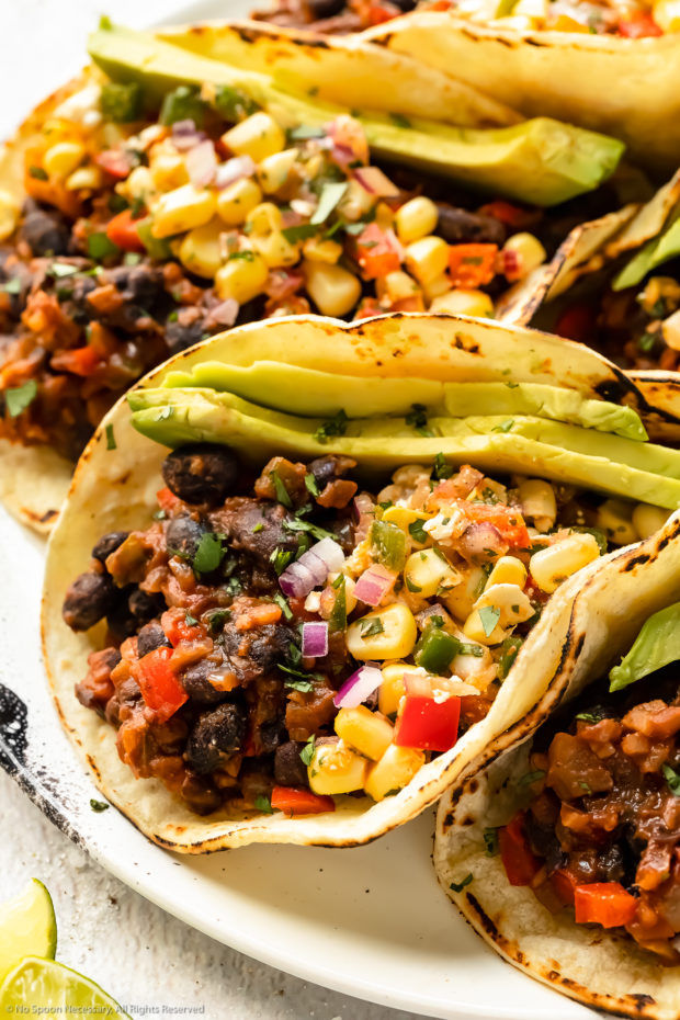 Angled close-up photo of black bean tacos topped with corn salsa and slices of avocado on a white plate.