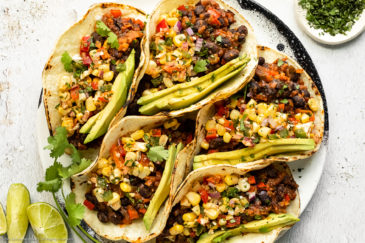 Overhead landscape photo of black bean tacos topped with corn salsa and slices of avocado on a white plate with a ramekin of chopped cilantro and fresh lime wedges next to the plate.