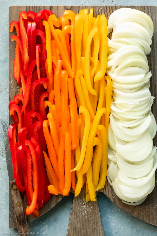 Overhead photo of thinly sliced peppers and onions on a gray wood cutting board - photo of how to cut vegetables for sauteing.