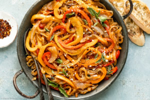 Overhead photo of Sauteed Peppers and Onions with two serving spoons inserted into the dish and slices of toasted baguette and a ramekin spicy red pepper flakes next to the pan.
