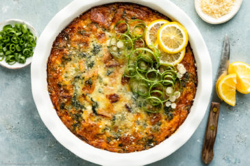 Overhead photo of Crustless Spinach Bacon Quiche garnished with fresh lemon slices and scallions in a white pie pan with a ramekin of sliced scallions and grated parmesan next to the quiche.