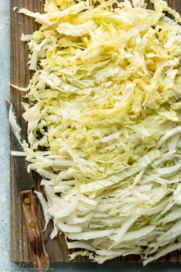 Overhead photo of shredded napa cabbage on a gray wood cutting board with a knife laying next to the cabbage