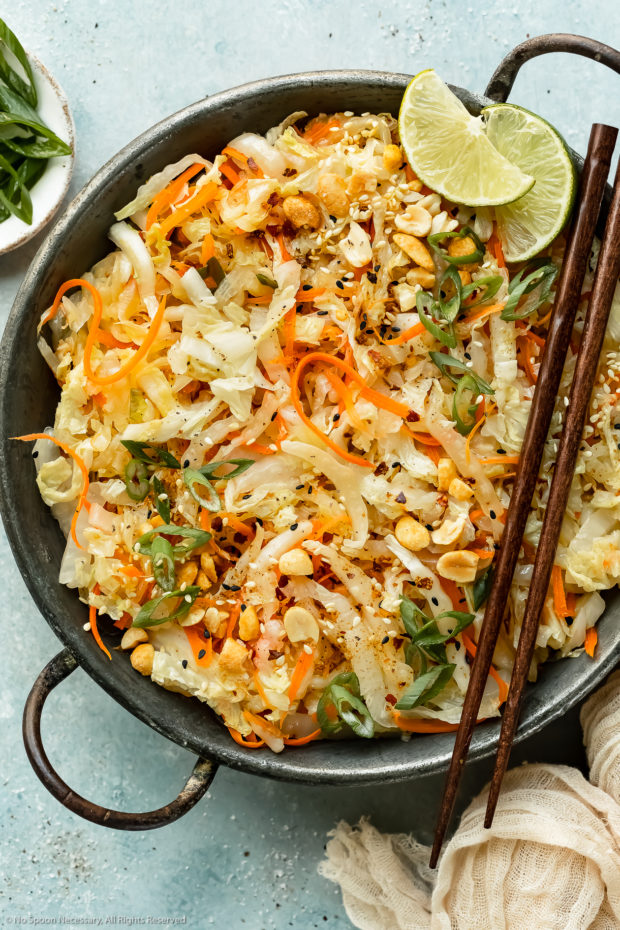 Overhead photo of stir-fried cabbage and carrots garnished with chopped peanuts and lime wedges in an antique skillet with chopsticks resting on the side of the skillet and a ramekin of sliced scallions next to the pan.