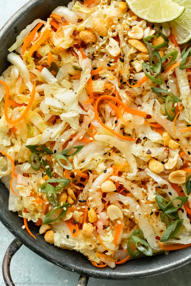 Overhead, up close photo of stir fried cabbage and carrots garnished with chopped peanuts and lime wedges in an antique skillet.