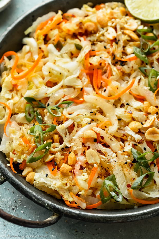 Angled, up close photo of stir fried cabbage garnished with chopped peanuts and lime wedges in an antique skillet.