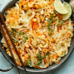 Overhead landscape photo of stir-fried cabbage and carrots garnished with chopped peanuts and lime wedges in an antique skillet with chopsticks resting on the side of the skillet and a ramekin of sliced scallions next to the pan.