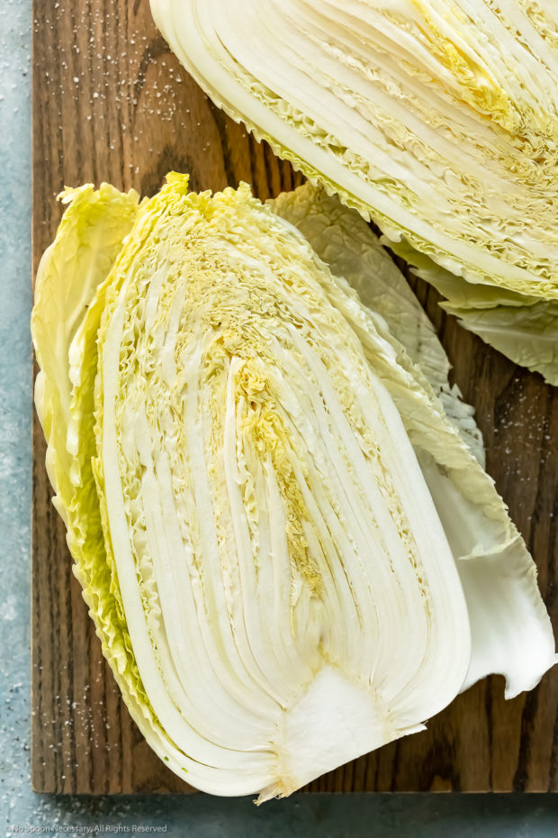 Overhead photo of a head of napa cabbage cut into half to expose the inside on a gray wood cutting board.