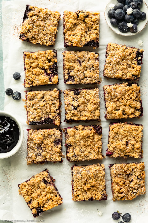 Overhead photo of blueberry bars cut into squares on a large piece of parchment paper with a ramekins of fresh blueberries and homemade blueberry pie filling next to the bars.