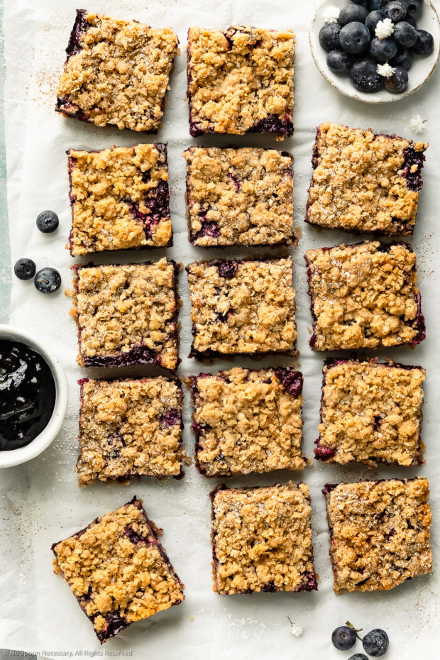 Overhead photo of blueberry crumb bars cut into squares on a large piece of parchment paper with a ramekins of fresh blueberries and homemade blueberry pie filling next to the bars.