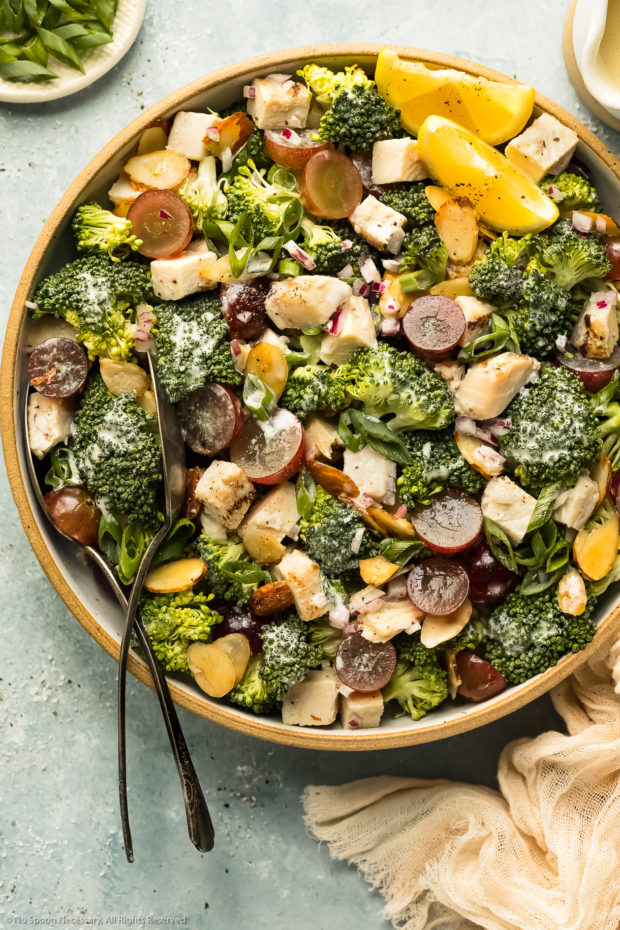 Overhead photo of the best broccoli grape salad in a large serving bowl with serving spoons inserted into the salad.