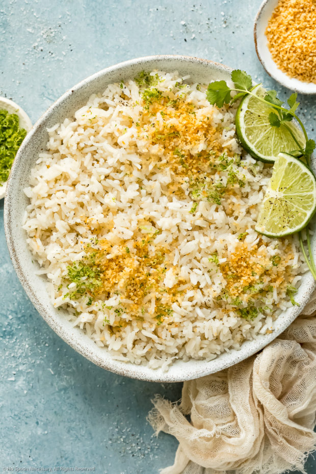 Overhead photo of easy coconut rice garnished with toasted coconut flakes and fresh lime zest in a white bowl with ramekins of lime zest and coconut flakes next to the bowl.