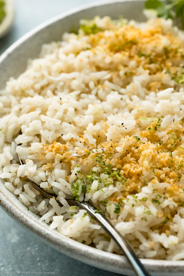 Angled, up-close photo of coconut milk Jasmine rice garnished with fresh lime zest and toasted coconut flakes in a white bowl with a serving spoon inserted into the rice.