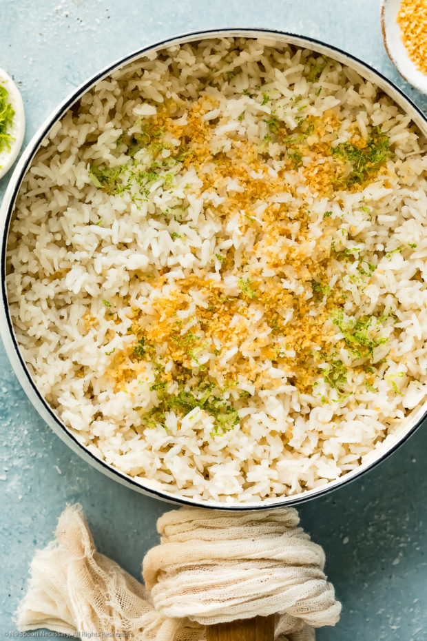 Overhead photo of rice cooked in coconut milk in a medium white saucepan with ramekins of lime zest and toasted coconut flakes next to the pan.