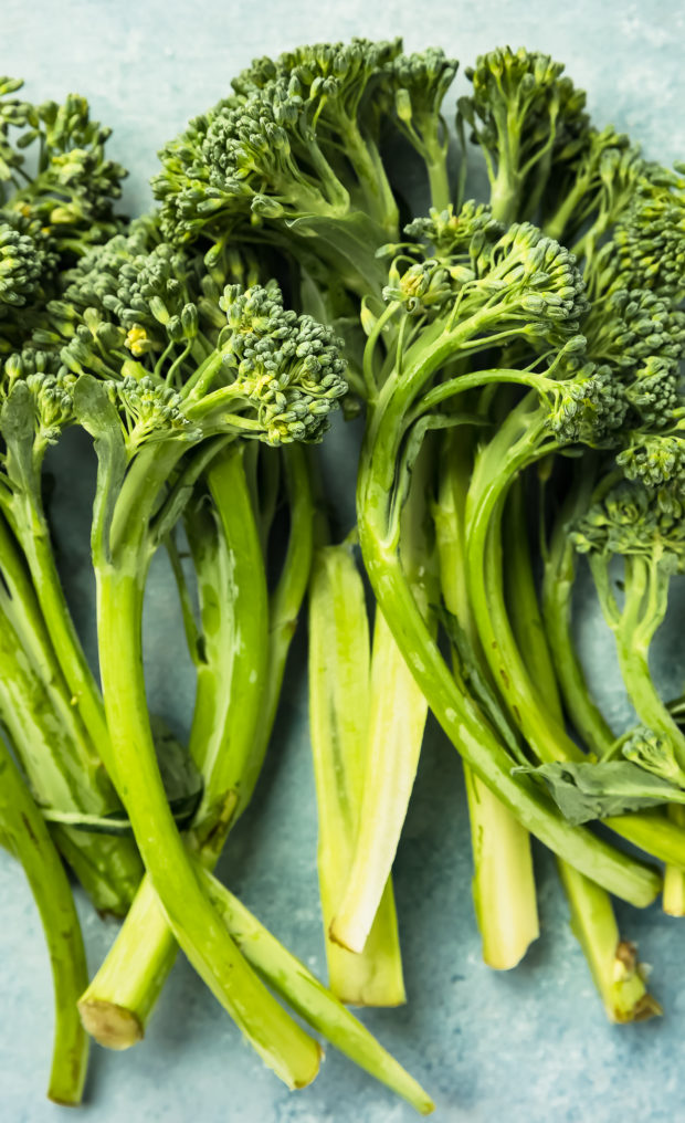 Overhead photo of a four bunches of fresh broccolini (hybrid broccoli) on a blue surface.