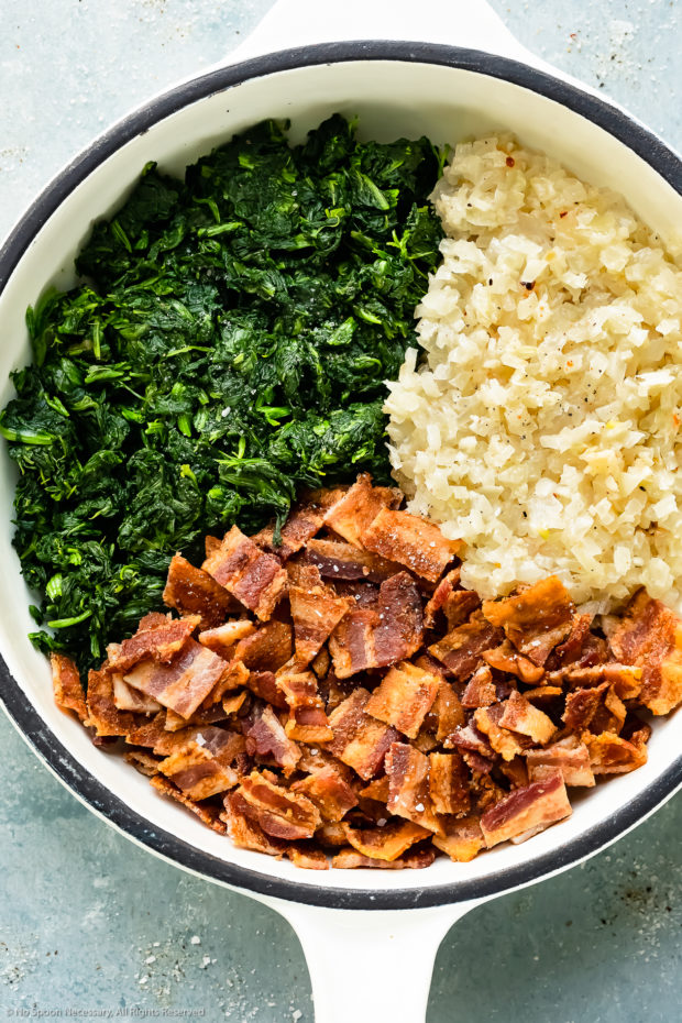 Overhead photo of sautéed onions, cooked bacon and chopped spinach in a white skillet - photo of the prepared vegetable filling for crustless quiche.