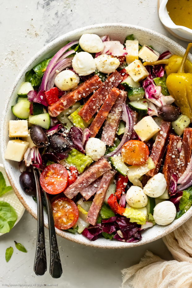 Overhead photo of Italian Chopped Salad in a white bowl with serving spoons inserted into the salad and a jar of homemade Italian dressing and a pale tan napkin arranged around the bowl.