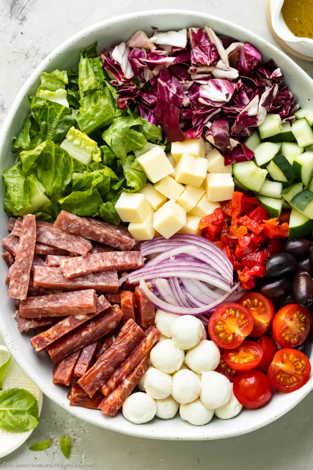 Overhead photo of the Italian chopped salad ingredients neatly arranged in a large serving bowl before being tossed with dressing.