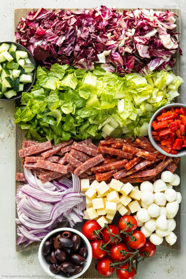 All of the ingredients to make a chopped Italian salad prepped and neatly arranged on a large wood cutting board - photo of all the ingredients needed to make the recipe.