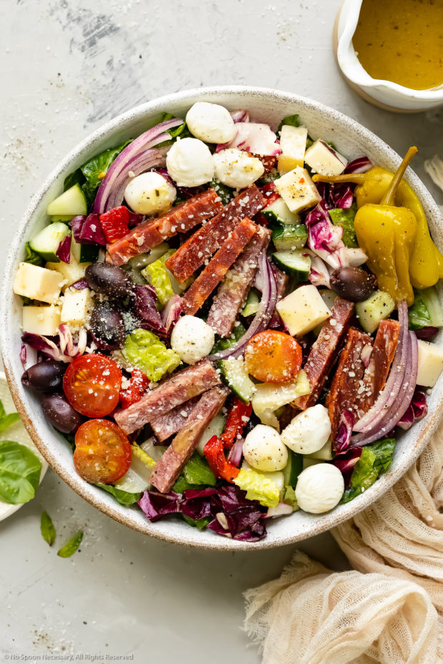 Overhead photo of Italian Chopped Salad in a white bowl with a jar of homemade Italian dressing, a pale tan napkin and a ramekin of fresh basil arranged around the bowl.
