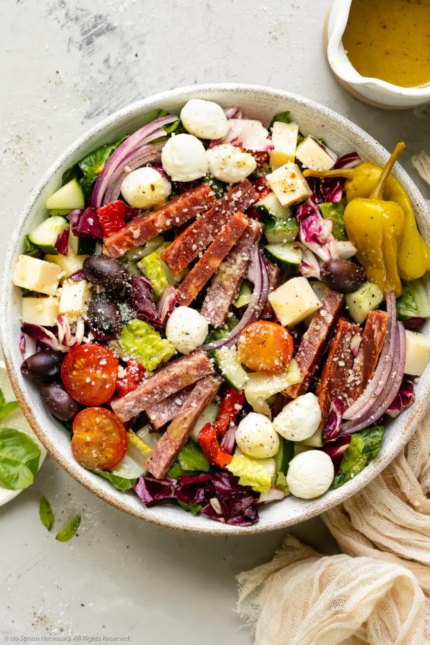 Overhead photo of Italian Chopped Salad in a white bowl with a jar of homemade Italian dressing, a pale tan napkin and a ramekin of fresh basil arranged around the bowl.