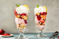 Straight on, landscape shot of a Strawberry Shortcake Sundae with another sundae directly next to it and slightly blurred, and spoons, coarse salt, and a small ramekin of sliced strawberries surrounding the sundae glass.