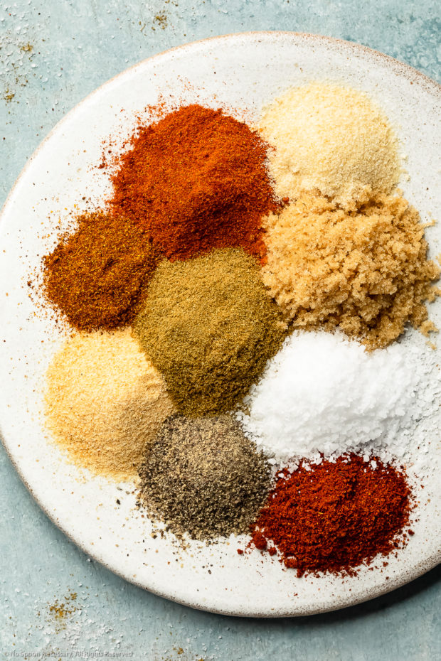 Overhead photo of all the seasonings needed to make BBQ spice rub neatly organized by individual seasoning on a white plate.