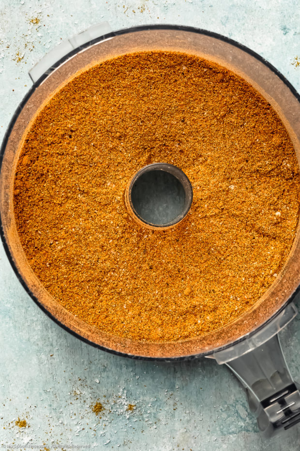 Overhead photo of BBQ dry rub seasonings in the bowl of a food processor after being ground together to create a fine powder.